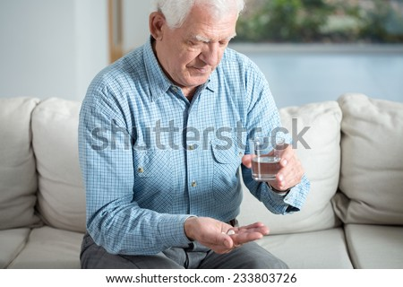 Ill senior man taking pill and drinking water - stock photo