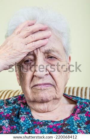 ill senior woman has headache - stock photo