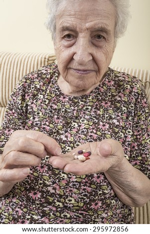 ill senior woman taking pill - stock photo