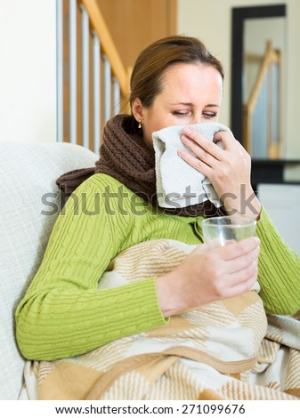 Ill woman sitting on a sofa at home. She hold a glass of hot drink in her hands and is blowing her nose in a wrap - stock photo