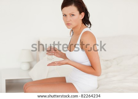 Ill woman taking pills in her bedroom