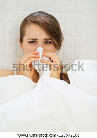 Ill woman with hanky laying in bed - stock photo