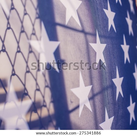 Illegal immigration concept  Background of transparent American flag behind a chain link fence and concrete stairway  - stock photo