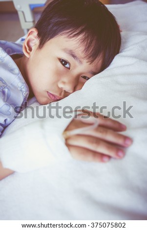 Illness asian boy lying on sickbed and looking at camera in hospital, saline intravenous (IV) on hand, shallow depth of field (DOF) face in focus, saline intravenous (IV) out of focus. Retro style. - stock photo