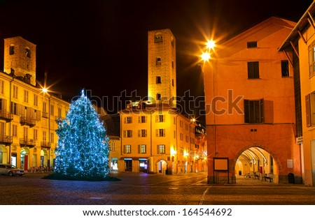 Illuminated and decorated Christmas Tree on city central square surrounded by old houses and medieval towers at night in Alba, Italy. - stock photo