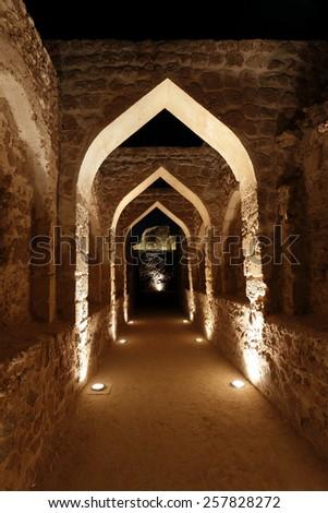Illuminated archway inside Bahrain fort - stock photo