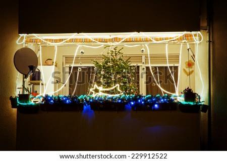 Illuminated balcony of a house on christmas - stock photo