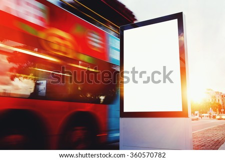 Illuminated blank billboard with copy space for your text message or content, public information board outdoors with motion blur bus on background, advertising mock up banner in metropolitan city - stock photo