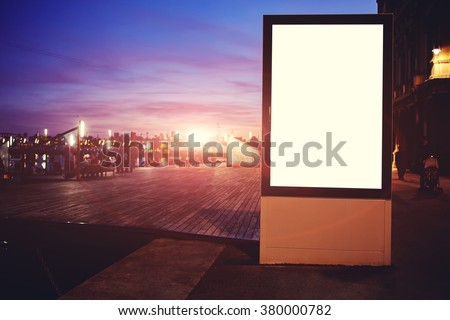 Illuminated blank billboard with copy space for your text message or promotional content, public information board in night in urban setting, advertising mock up banner in metropolitan city  - stock photo