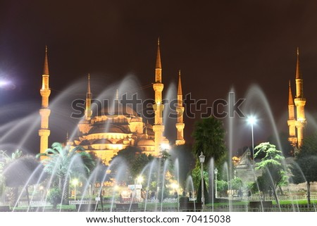 Illuminated Blue Mosque in Istanbul behind fountain at night - stock photo
