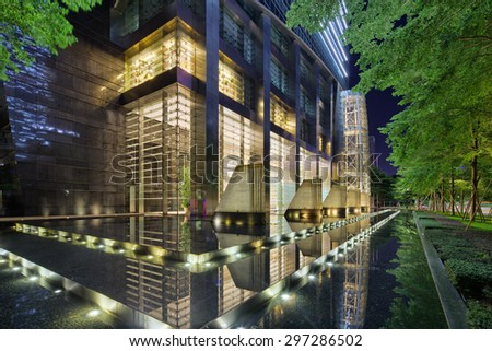Illuminated building exterior and footpath - stock photo