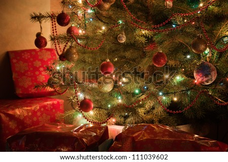 Illuminated Christmas tree at night with presents- parth of tree - stock photo