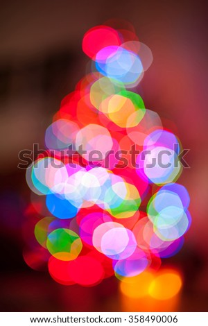 Illuminated christmas tree shaped  blurred bokeh light background. Multicolored vertical image. - stock photo