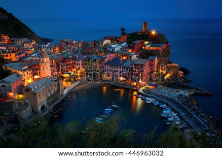 Illuminated, colorful village Vernazza, world heritage site in evening,mirroring lights in the sea, deep blue sky,colorful houses, some of the most dramatic coastal scenery.  Cinque terre, Italy. - stock photo