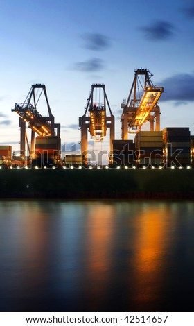 Illuminated container ship being unloaded by three large cranes at twilight in the Rotterdam Harbor - stock photo