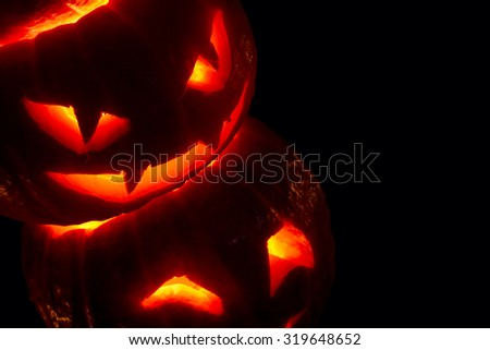 Illuminated cute halloween pumpkins isolated on black background