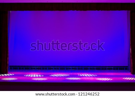 Illuminated empty theater stage - stock photo