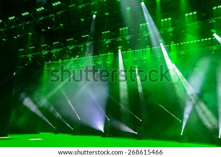 Illuminated empty theater stage with fog and rays of green light - stock photo