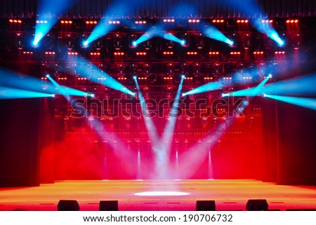 Illuminated empty theater stage with smoke - stock photo