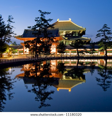 Illuminated evening view of the gate and wall surrounding Todai-ji temple with a pond in the foreground in Nara, Japan.  Todai-ji temple can be seen in the background behind the wall.