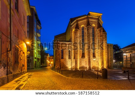 Illuminated facade of catholic church on narrow cobbled street at early morning in Alba, Italy. - stock photo