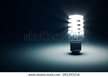 Illuminated Fluorescent Light Bulb on blue dark background with place for Your Text - stock photo