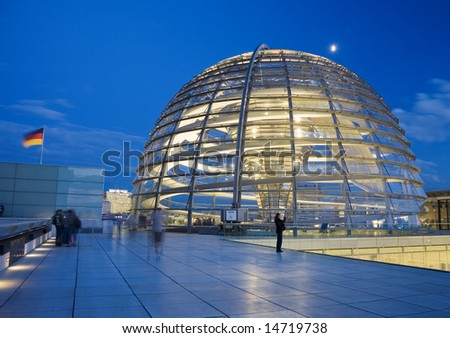 Illuminated glass dome on the roof of the Reichstag in Berlin in the evening - stock photo