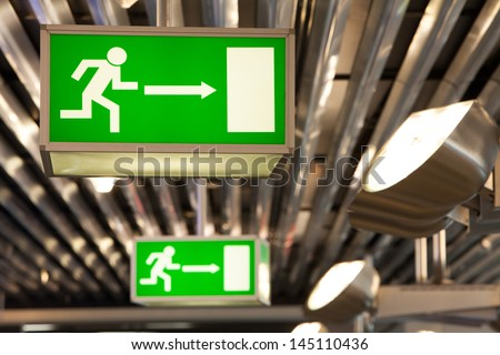 Illuminated green exit signs attached to the ceiling in a public transportation facility. Signage of a human figure running and exiting through a door opening. Lights shine on ceiling and the signs.