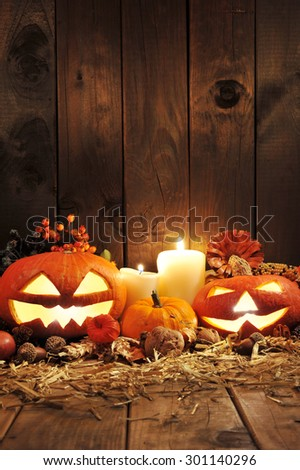 illuminated halloween pumpkins, candles, nuts, maize-cob and apple on straw in front of old weathered wooden board in candlelight - stock photo