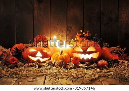 illuminated halloween pumpkins, candles, nuts, maize-cob and apple on straw in front of old weathered wooden board in candlelight