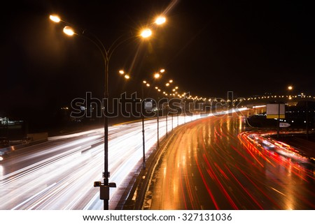 Illuminated highway at night with light trails.