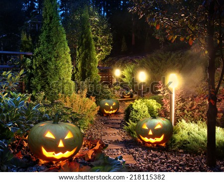 Illuminated home garden path patio lights with halloween pumpkin lanterns - stock photo
