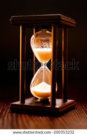Illuminated hourglass in a wooden frame with sand pouring through between the glass bulbs measuring the passing time against a dark background