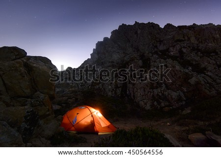 illuminated inside orange tent stood among the rocks on the Atlantic Ocean. Sintra , Portugal - stock photo