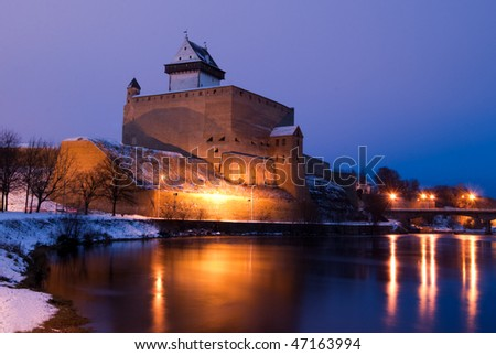 Illuminated Narva castle and reflection in water - stock photo