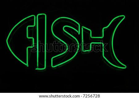 Illuminated neon sign in shape of fish - stock photo