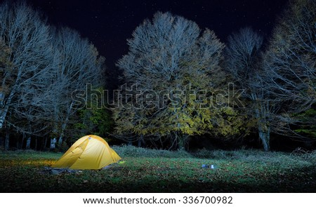 illuminated one person tent in the old forest of Nebrodi Park, Sicily - stock photo