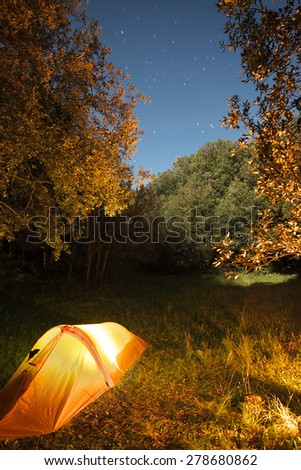illuminated one person tent in the woods of Etna Park under starry blue sky, Sicily - stock photo