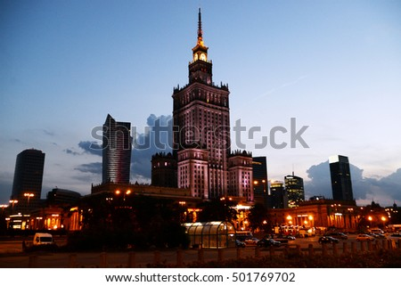 Illuminated Palace of Culture and Science in downtown of Warsaw, Poland. Modern business skyscrapers at night with sunset clear blue sky