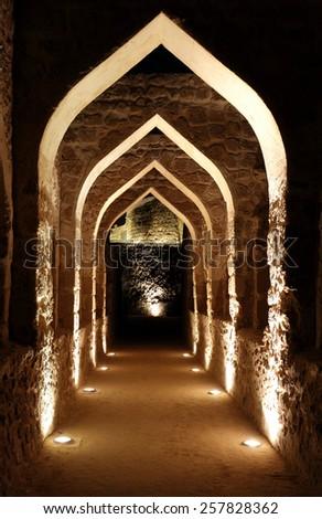 Illuminated passage inside Bahrain fort - stock photo