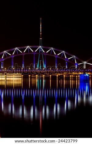 Illuminated Riga Railway bridge over river Daugava at night - stock photo