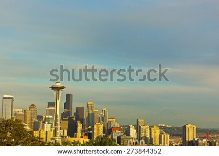 Illuminated Seattle skyscrapers and contour of Mount Rainier at sunset. Seattle city panorama on a sunny summer evening. - stock photo