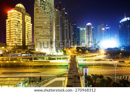 Illuminated skyline and buildings in modern city at night - stock photo