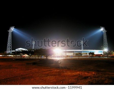 Illuminated stadium at night from parking lot. - stock photo