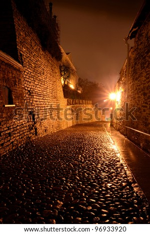 Illuminated street in old part of Tallinn by night - stock photo