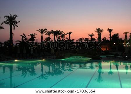 Illuminated swimming pool in Turkish resort by night - stock photo