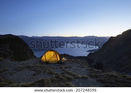 Illuminated tent by the lakeshore at dusk - stock photo