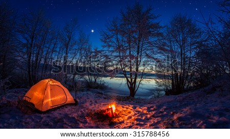Illuminated tent in the winter camp by the lake at night - stock photo