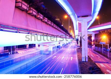 illuminated traffic on elevated expressway in modern city - stock photo