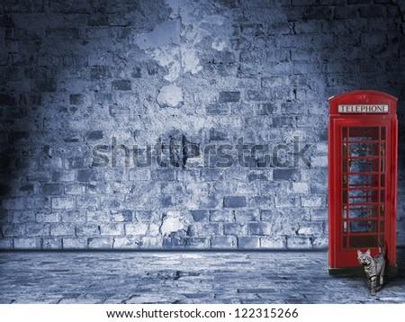 illuminated vintage wall and street design with british phone box and tomcat - stock photo